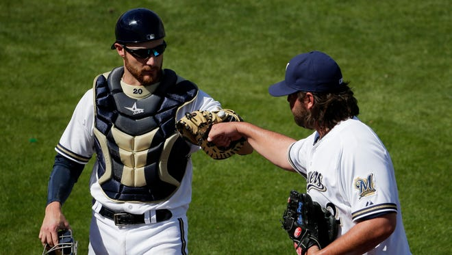 Brewers relief pitcher Chris Perez, right, celebrates the end of an inning with catcher Jonathan Lucroy, while avoiding hand-to-hand contact.