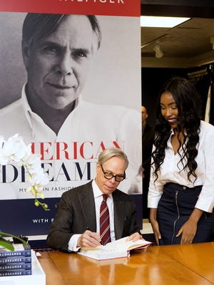 "Fashion designer and Elmira native Tommy Hilfiger signs a copy of his new book, ""American Dreamer: My Life in Fashion & Business,"" for a fan at the Hilfiger store in Corning."