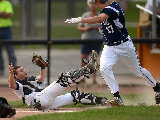 Bay Port's Vann Jacques (17) avoids being tagged by Green Bay Preble catcher Nick Baldschun (16) during a play at home plate in Thursday's baseball game at Joannes Stadium in Green Bay.