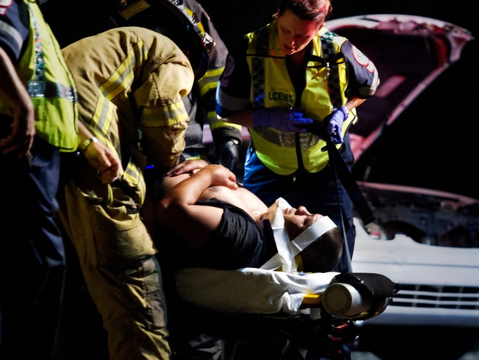 Emergency personnel care for a man involved in a three-vehicle crash involving a deputy on I-75 half a mile south of Alico Road. According to Deputy T.J. Brown of the Lee County Sheriff's Office, a deputy was conducting a DUI traffic stop around 9:40 p.m. Wednesday on Interstate 75 northbound, south of Alico Road. While the deputy was at a truck pulled over for a DUI stop, two other vehicles crashed, subsequently crashing into the deputy's vehicle, an unmarked SUV. The deputy was not injured in the crash. The drivers of the vehicles in the initial crash had to be extracted after being trapped. Both drivers were transported to the hospital with minor injuries.