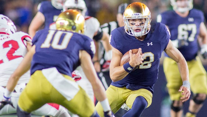 Fighting Irish quarterback Ian Book (12) runs the ball in the second half of the game against the Miami (Oh) Redhawks at Notre Dame Stadium.