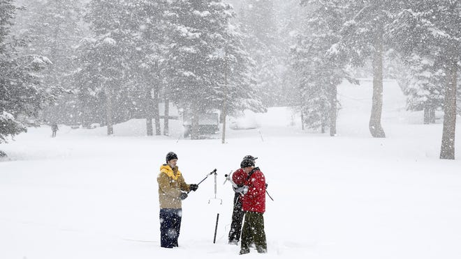 Frank Gehrke, right, chief of the California Cooperative Snow Surveys Program for the Department of Water Resources, prepares to do the first sample of the second manual snow survey of the season at Phillips Station near Echo Summit, Tuesday, Feb. 2, 2016. The survey showed the snowpack at 130 percent of normal for this site at this time of year. Gehrke was accompanied by Michael Jarred, left, a consultant with Assembly Natural Resources Committee, and Kasey Schimke, of the DWR.