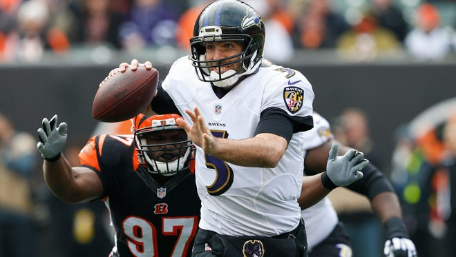Baltimore Ravens quarterback Joe Flacco looks to pass under pressure from Cincinnati Bengals defensive tackle Geno Atkins (97)  on Jan. 1, 2017, in Cincinnati.
