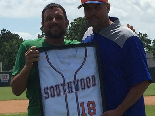 Justin Mouser (left), the father of the late Jacob Meshell, holds up the retired Southwood baseball jersey of his son, with Southwood baseball coach Aaron Vorachek.
