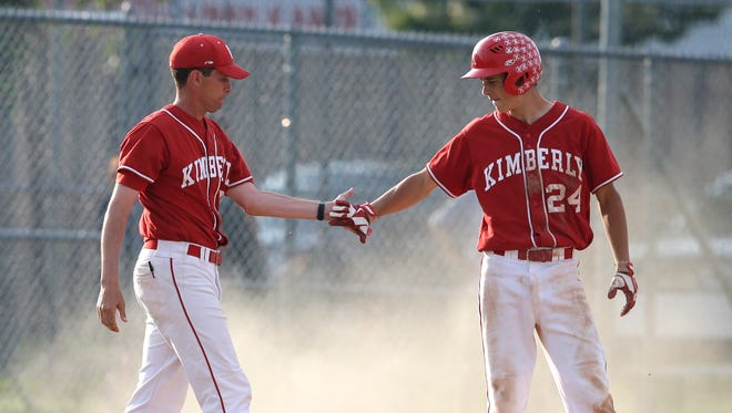 Kimberly High School's coach Ryan McGinnis, left, congratulates Ben Carew after he hit a triple against West De Pere High School during their WIAA Division 1 baseball sectional championship game Tuesday, June 9, 2015, at Nienhaus Sports Complex in Appleton, Wis.