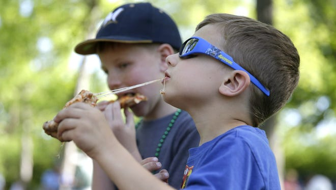 Dane Krutz, 5, and his brother Jameson Thompson, 9, dig into some pizza during a food truck rally in Pierce Park in May 2016 in Appleton.