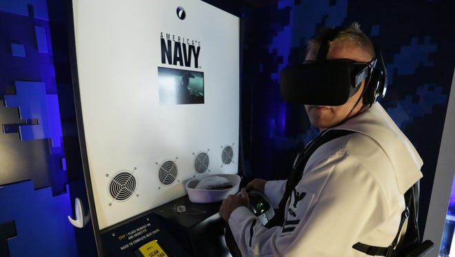 Petty Officer Maxwell Molidor, a Navy recruiter stationed in Sheboygan, participates Thursday in a Navy virtual reality simulation at  Experimental Aircraft Association AirVenture in Oshkosh.