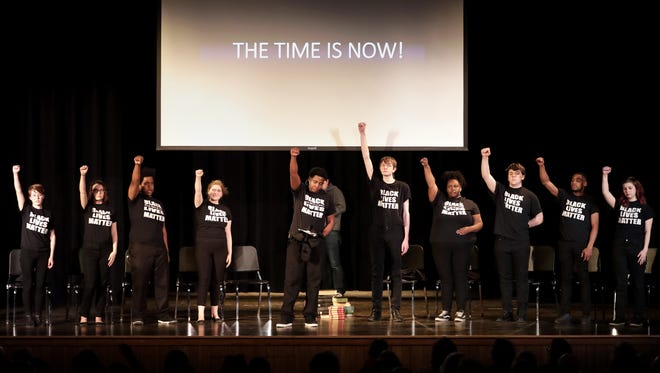 """The cast of """"In White America"""" from Rufus King High School raise their fists at the close of the play Wednesday at River View Middle School in Kaukauna. The play was originally performed in the same building, which then was Kaukauna High School, in 1966."""