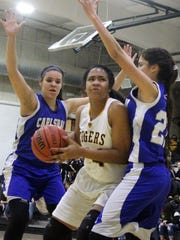 Alamogordo's Jerraysha Smith drives toward the basket while being heavily defended on Friday night at the Tiger Pit.