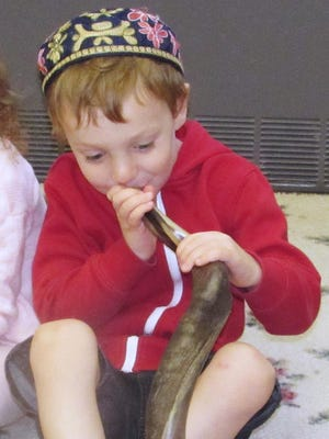 Eytan Steinitz, 5, son of Rabbi Oren Steinetz, tries blowing the shofar Sunday morning in the Jewish Community School at Congregation Kol Ami.