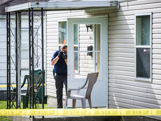 A Muncie police officer inspects the scene of a fatal