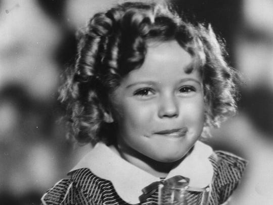 Hollywood actress Shirley Temple has died at the age of 85. The American child star started performing in films at three years of age. She entered politics in the 1960s and took on several ambassador positions representing her country. Pictured, smiling and holding louvred doors around her.