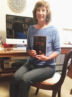 """Janet Nichols Lynch poses with her latest book """"Wheel of Fire"""" in her writing room.  Born and raised in Sacramento, California, Janet is the author of eleven books.  Her latest YA novels are My Beautiful Hippie (Holiday House, 2013), set in the Haight-Ashbury during the 1960s, and  Racing California (Holiday House, 2012) set at the Amgen Tour of California, the most prestigious professional cycling stage race in the U.S.  Her other works include three other YA novels, Addicted to Her (Holiday House 2010), Messed Up (Holiday House, 2009) and Peace is a Four-letter Word (Heyday, 2005), a mainstream novel Chest Pains (Bridge Works, 2009), a short story collection, Where Words Leave Off Music Begins (iUniverse, 2004), two nonfiction books about music for young readers, American Music Makers: An Introduction to American Composers (Walker, 1990) and Women Music Makers:  An Introduction to Women Composers (Walker, 1992), and the juvenile novel Casey Wooster's Pet Care Service (Atheneum, 1993)."""