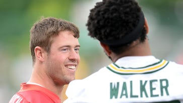 Green Bay Packers quarterback Scott Tolzien (16) smiles as he talks with Josh Walker (79) during minicamp at Clarke Hinkle Field June 18, 2015.
