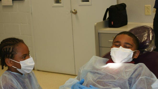 Quarter Mile Lane School student Jamiel Carter-Matthews (left) gets ready to practice dental assisting on classmate Eric White during a visit to Cumberland County Technical Education Center.