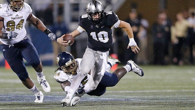 MIAMI, FL - SEPTEMBER 24: Mckenzie Milton #10 of the Central Florida Knights runs with the ball past the attempted tackle by Milord Juste #46 of the Florida International Golden Panthers on September 24, 2016 at FIU Stadium in Miami, Florida. (Photo by Joel Auerbach/Getty Images)