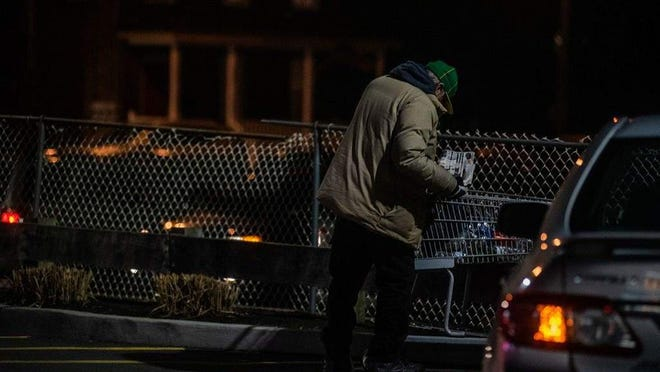 A homeless man takes belongings out of a shopping cart in the McDonald's parking lot in teh City of Newburgh in January. Homelessness is increasing in Newburgh.