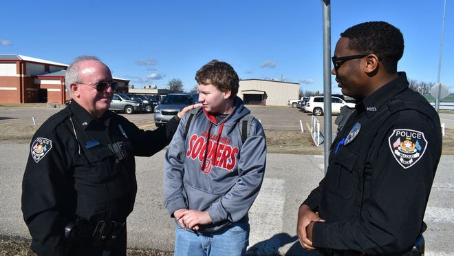 From left to right Mcloud Schol Resource Officer (SRO) with one of the several students he keeps safe and fellow SRO Marcus Burris.