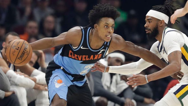 """From March 2, 2020, Cleveland Cavaliers' Collin Sexton, left, drives past Utah Jazz's Mike Conley in the first half of an NBA basketball game in Cleveland. When Sexton learned that the NBA _ and not a virus _ had ended his second season, the Cavaliers guard had a guttural reaction. """"I was sick,"""" he said. The league's decision to only invite 22 teams to resume play at Disney World in Florida next month was a body blow for players on the omitted squads _ aka the Delete 8. And although they've had time to process the exclusion, Sexton, Cavs star forward Kevin Love and their teammates, are still struggling with the reality that their season is over."""