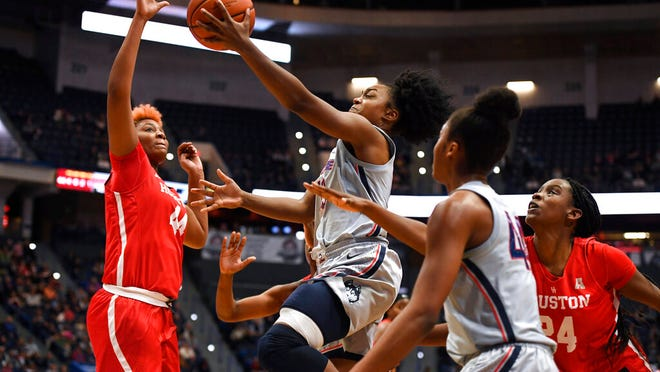 Connecticut's Christyn Williams, center, goes up for a basket as Houston's Jazmaine Lewis, left, and Houston's Maya Jones, right, defend, in the second half of an NCAA college basketball game, Saturday, Jan. 11, 2020, in Hartford, Conn.