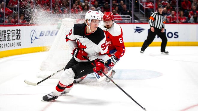 New Jersey Devils center Jesper Boqvist (90), from Sweden, moves the puck past Washington Capitals defenseman Michal Kempny (6), from the Czech Republic, during the third period of an NHL hockey game Saturday, Jan. 11, 2020, in Washington. The Devils won 5-1.
