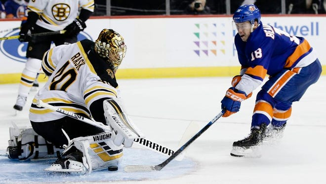 Boston Bruins goaltender Tuukka Rask (40) stops a shot on goal by New York Islanders' Anthony Beauvillier (18) during the second period of an NHL hockey game Saturday, Jan. 11, 2020, in New York.