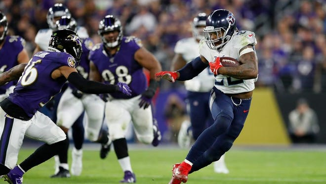 Tennessee Titans running back Derrick Henry (22) runs past Baltimore Ravens players during the second half of an NFL divisional playoff football game, Saturday, Jan. 11, 2020, in Baltimore.