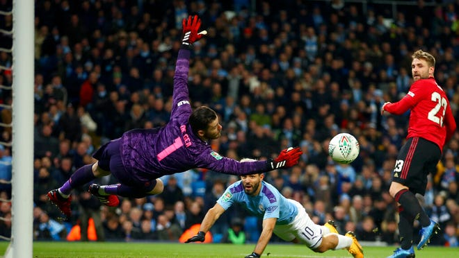 Manchester United's goalkeeper David de Gea dives for the ball in front of Manchester City's Sergio Aguero, center, and Manchester United's Luke Shaw, right, during the English League Cup semifinal second leg soccer match between Manchester City and Manchester United at Etihad stadium in Manchester, England, Wednesday, Jan. 29, 2020.
