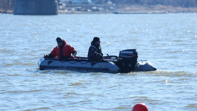 State police divers search the Hudson River on Wednesday for the weapon used in the triple homicide in the Town of Newburgh on Sunday.