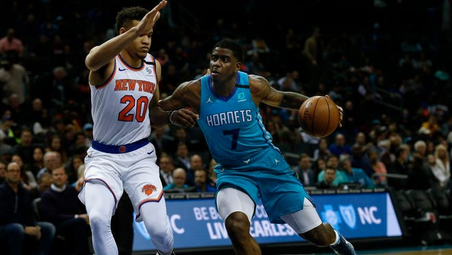Charlotte Hornets guard Dwayne Bacon, right, drives into New York Knicks forward Kevin Knox II in the first half of an NBA basketball game in Charlotte, N.C., Tuesday, Jan. 28, 2020.