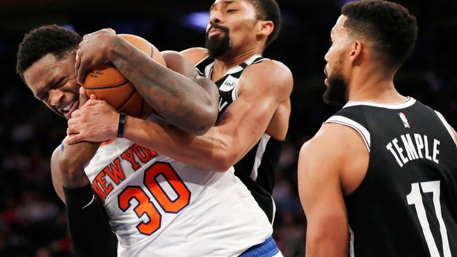 Brooklyn Nets guard Garrett Temple (17) watches as New York Knicks forward Julius Randle (30) and Nets guard Spencer Dinwiddie, center, struggle for control of the ball beneath the Nets' basket during the second half of an NBA basketball game in New York, Sunday, The Knicks defeated the Nets 110-97.