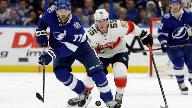 Tampa Bay Lightning defenseman Victor Hedman (77) moves the puck in front of Florida Panthers center Noel Acciari (55) during the first period of an NHL hockey game Monday, Dec. 23, 2019, in Tampa, Fla.