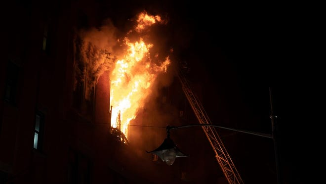 Fire blows out of a window in the Chinatown section of New York, Thursday, Jan. 23, 2020. New York City firefighters battled a raging blaze at a building in the city's Chinatown area Thursday night, Firefighters said they were called about 8:45 p.m. to 70 Mulberry Street for a fire on the fourth and fifth floors of the building, NYFD officials said.