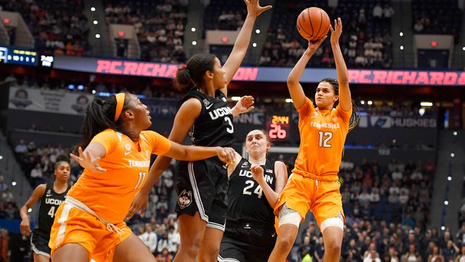 Tennessee's Rae Burrell (12) shoots over Connecticut's Megan Walker (3) and Connecticut's Anna Makurat (24) as Tennessee's Kasiyahna Kushkituah (11) defends in the first half of an NCAA college basketball game, Thursday, Jan. 23, 2020, in Hartford, Conn.