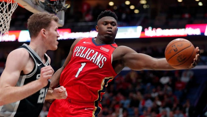 New Orleans Pelicans forward Zion Williamson (1) pulls in a rebound against San Antonio Spurs center Jakob Poeltl (25) in the second half of an NBA basketball game in New Orleans, Wednesday, Jan. 22, 2020. The Spurs won 121-117.