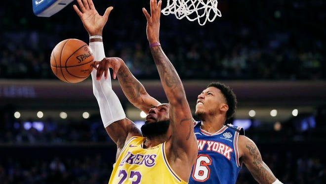 New York Knicks guard Elfrid Payton (6) tips the ball away from Los Angeles Lakers forward LeBron James (23) during the first half of an NBA basketball game in New York, Wednesday, Jan. 22, 2020.