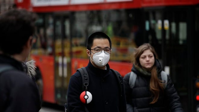 A man wearing a face mask walks backdropped by a red London bus across the street from the Bank of England in London, Wednesday, March 4, 2020. British authorities laid out plans Tuesday to confront a COVID-19 epidemic, saying that the new coronavirus could spread within weeks from a few dozen confirmed cases to millions of infections, with thousands of people in the U.K. at risk of death.