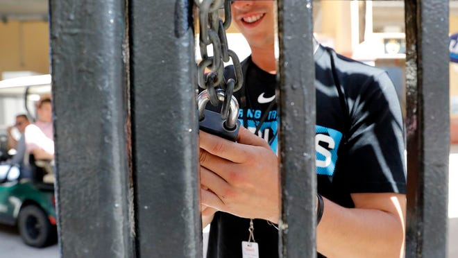 An employee of Roger Dean Stadium locks a gate, Friday, March 13, 2020, in Jupiter, Fla. Major League Baseball has delayed the start of its season by at least two weeks because of the coronavirus outbreak as well as suspended the rest of its spring training game schedule.