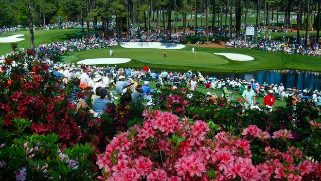 From April 4, 2011, golf fans watch practice on the par three 16th hole during a practice round for the Masters at Augusta National Golf Club in Augusta, Ga. Augusta National decided Friday, March 13, 2020, to postpone the Masters because of the spread of the coronavirus. Club chairman Fred Ridley says he hopes postponing the event puts Augusta National in the best position to host the Masters and its other two events at some later date. Ridley did not say when it would be held.