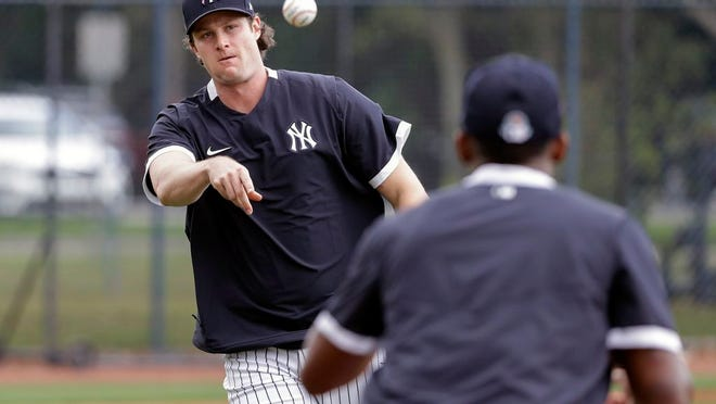New York Yankees' Gerrit Cole throws to first base during a drill at a spring training baseball workout Thursday, Feb. 20, 2020, in Tampa, Fla.