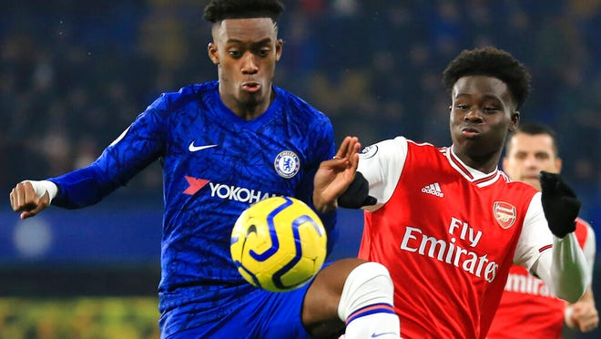 Chelsea's Callum Hudson-Odoi, left, fights for the ball with Arsenal's Bukayo Saka during the English Premier League soccer match between Chelsea and Arsenal at Stamford Bridge stadium in London England, Tuesday, Jan. 21, 2020.