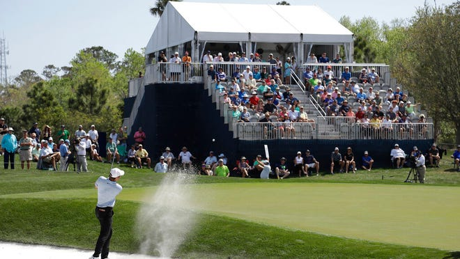 A small crowd watches Scottie Scheffler hit from the sand on the eighth hole, during the first round of The Players Championship golf tournament Thursday, March 12, 2020, in Ponte Vedra Beach, Fla.