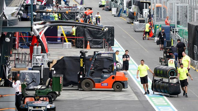 Workers pack up in pit lane after the cancellation of the Australian Formula One Grand Prix in Melbourne, Friday, March 13, 2020. The first F1 Grand Prix of the season was canceled two hours before the first official practice was set to start Friday after organizers relented to pressure to call it off amid the spreading coronavirus.