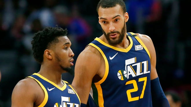 From March 7, 2020, Utah Jazz center Rudy Gobert (27) talks with guard Donovan Mitchell, left, during the second half of an NBA basketball game against the Detroit Pistons, in Detroit. Both players have tested positive for the coronavirus.  Gobert's test result forced the NBA to suspend the season.
