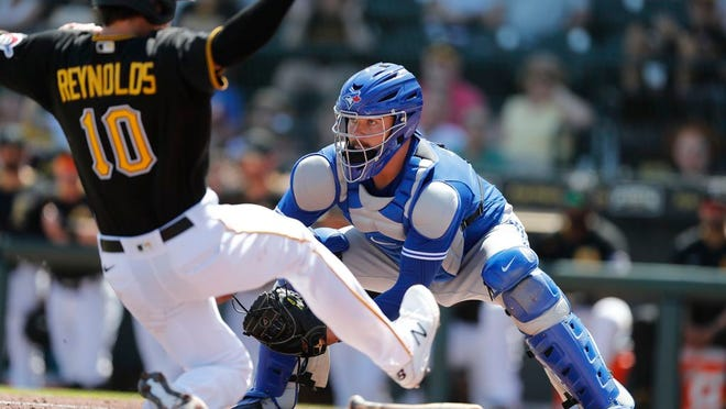 Toronto Blue Jays catcher Reese McGuire waits on the throw as Pittsburgh Pirates' Bryan Reynolds begins his slide during a spring training baseball game, Thursday, March 12, 2020, in Bradenton, Fla.