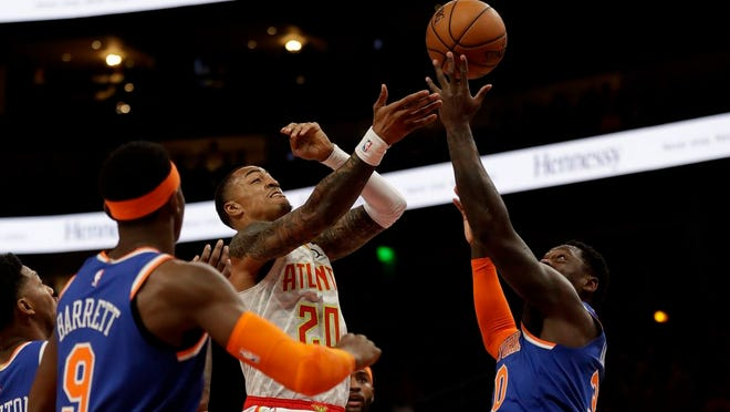 Hawks forward John Collins (20) battles Knicks forward Julius Randle (30) as he drives to the basket during the first half.