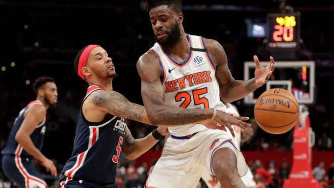 Washington Wizards' Shabazz Napier, front left, knocks the ball away from New York Knicks' Reggie Bullock (25) during the first half of an NBA basketball game Tuesday, March 10, 2020, in Washington.