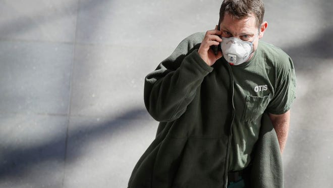 A pedestrian wears a face mask in the World Financial Center complex, Monday, March 9, 2020, in New York. New York continued grappling Monday with the new coronavirus, as case numbers, school closings and other consequences grew.