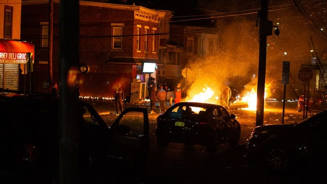 Dozens of people light various objects on fire in the middle of Carpenter and 1st street Newburgh, NY on March 28, 2020. Tensions were high after police shot and killed a man on William street earlier in the day. ALLYSE PULLIAM/For the Times Herald-Record