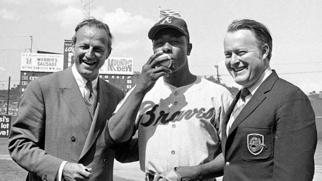 From May 17, 1970, Atlanta Braves' Hank Aaron, center, who became the ninth player in Major League history to get 3,000 hits, kisses a baseball alongside Famer Stan Musial and Braves owner Bill Bartholomay, in Cincinnati. Bartholomay, the former Braves owner who moved the team from Milwaukee to Atlanta in 1966, died Wednesday, March 25, 2020, at New York-Presbyterian Hospital, according to his daughter, Jamie. He was 91. Bartholomay sold the Braves to Ted Turner in 1976 but remained as chairman of the team's board of directors until 2003, when he assumed an emeritus role.